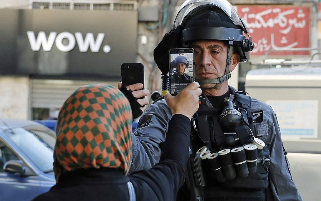A Palestinian woman takes a picture of a member of the Israeli security forces as he takes her picture in a street in Jerusalem on December 16, 2017(AFP PHOTO / AHMAD GHARABLI)