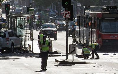 A white SUV sits in the middle of the road as police and emergency personnel work at the scene of where a car ran over pedestrians in Flinders Street in Melbourne on December 21, 2017. (AFP/ Mark Peterson)