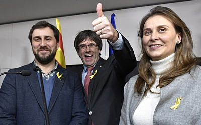 Axed Catalan president Carles Puigdemont, flanked by former Catalan Health minister Antoni Comin, left, and former Catalan Minister of Agriculture, Livestock, Fisheries and Food Meritxell Serret, reacts after the results of the regional elections in Catalonia  in Brussels on December 21, 2017. (AFP/ JOHN THYS)