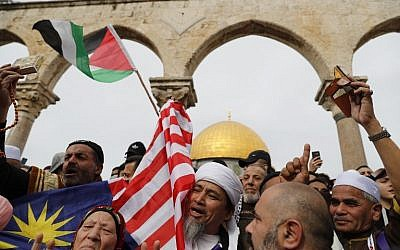 Illustrative: Muslim worshipers hold Palestinian and Malaysian flags following Friday noon prayers At Jerusalem's Old City's al-Aqsa mosque compound on the Temple Mount, December 22, 2017. (AFP Photo/Ahmad Gharabli)