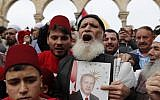 Muslim worshipers hold a portrait of Turkish President Recep Tayyip Erdogan following Friday noon prayer in Jerusalem's Old City's al-Aqsa mosque compound on the Temple Mount, December 22, 2017. (AFP Photo/Ahmad Gharabli)