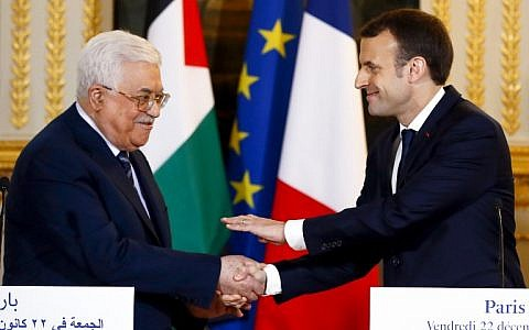 French President Emmanuel Macron (R) shakes hands with Palestinian Authority President Mahmoud Abbas at the end of a joint press conference following their meeting at the Elysee presidential Palace, in Paris, on December 22, 2017. (AFP/Pool/Francois Mori)