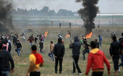 Illustrative: Palestinian protesters clash with Israeli soldiers near the border fence east of Gaza City on December 22, 2017. (AFP/Mohammed Abed)