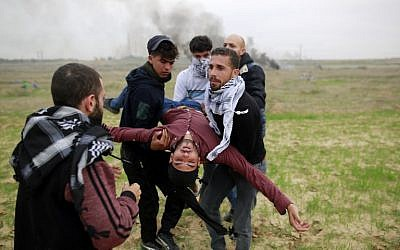 Palestinian protesters carry a wounded comrade during clashes with Israeli soldiers near the border fence east of Gaza City on December 22, 2017. (AFP PHOTO / MOHAMMED ABED)