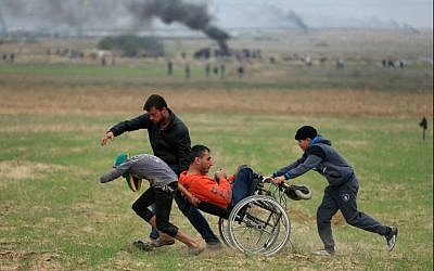 Palestinians assist a demonstrator in a wheelchair during clashes with Israeli security forces near the border fence east of Gaza City on December 22, 2017. (AFP Photo/Mohammed Abed)