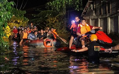 Rescue workers evacuate flood-affected residents in Davao on the southern Philippine island of Mindanao early on December 23, 2017, after Tropical Storm Tembin dumped torrential rains across the island. (AFP PHOTO / MANMAN DEJETO)