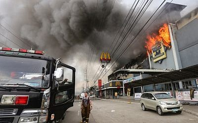 A firefighter stands in front of a burning shopping mall in Davao City on the southern Philippine island of Mindanao, December 23, 2017 (AFP PHOTO / MANMAN DEJETO)