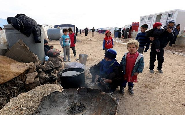 Syrians, forced to leave their homes in the eastern cities of Deir Ezzor and Raqa by the war against the Islamic State (IS) group, are seen outside a tent at the Ain Issa camp on December 18, 2017.  (AFP PHOTO / Delil Souleiman)