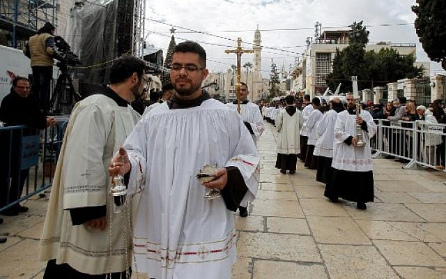 Roman Catholic deacons and clergymen walk in a procession prior to Christmas eve at the Manger Square outside the Church of the Nativity in the West Bank town of Bethlehem, December 24, 2017.  (Wisam Hashlamoun/Flash90)