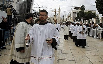 Roman Catholic deacons and clergymen walk in a procession prior to Christmas eve at the Church of the Nativity compound in the West Bank city of Bethlehem on December 24, 2017. (AFP PHOTO / Musa AL SHAER)