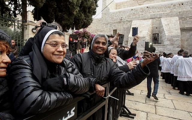 Nuns watch and use their cell phones to film a Roman Catholic procession prior to Christmas eve at the Manger Square outside the Church of the Nativity in the West Bank town of Bethlehem, December 24, 2017. (Wisam Hashlamoun/Flash90)