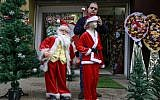 A Palestinian shopkeeper outfits mannequins with Santa Claus clothing outside his shop in Gaza City on December 25, 2017. (AFP Photo/Mohammed Abed)