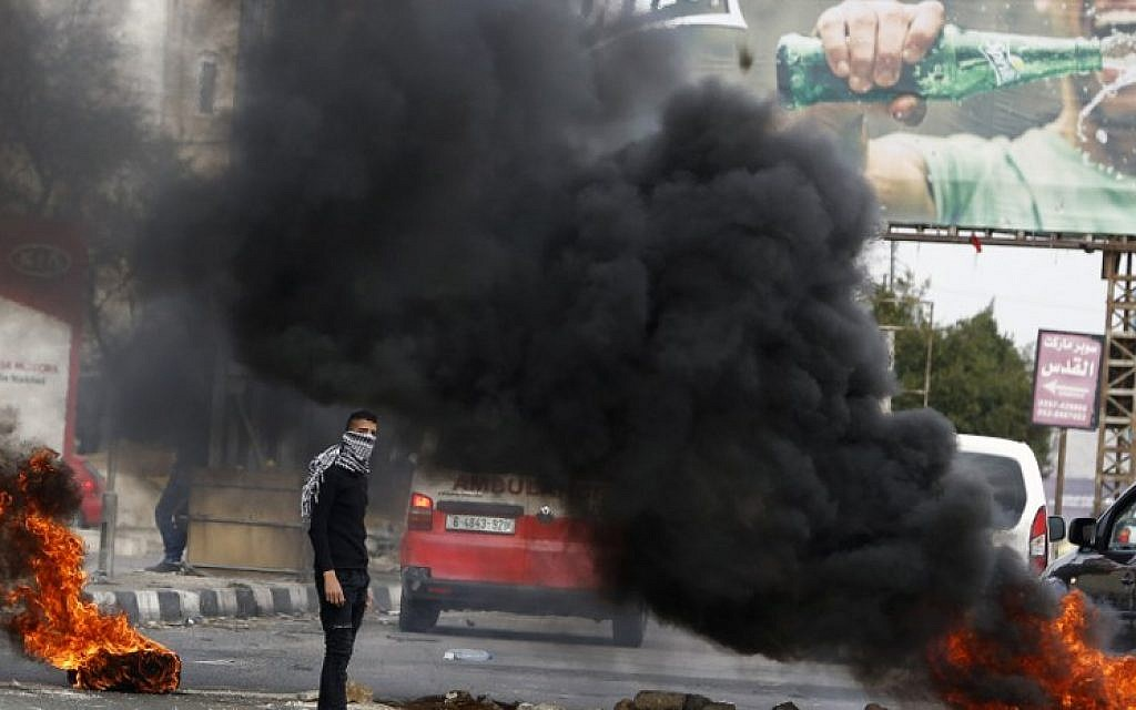 A Palestinian protester stands near flaming tires during clashes with Israeli soldiers near the Huwara checkpoint, south of Nablus in the Israeli-occupied West Bank on December 27, 2017. (AFP /JAAFAR ASHTIYEH)