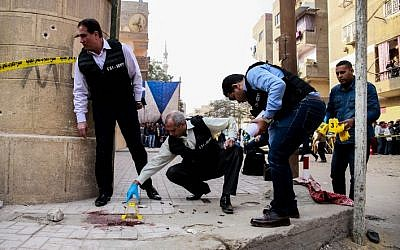 Egyptian security members and forensic police inspect the site of a gun attack outside a church south of the capital Cairo, on December 29, 2017. (AFP PHOTO / Samer ABDALLAH)