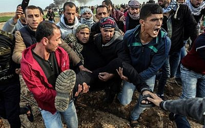 Palestinian protesters carry a wounded man during a clash with Israeli forces near the Israel-Gaza border east of the southern Gaza strip city of Khan Yunis on December 29, 2017. (AFP PHOTO / SAID KHATIB)