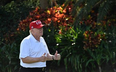 US President Donald Trump holds two thumbs up while meeting with service members of the United States Coast Guard to play golf at Trump International Golf Course in Mar-a-Lago, Florida on December 29, 2017. (AFP PHOTO / Nicholas Kamm)