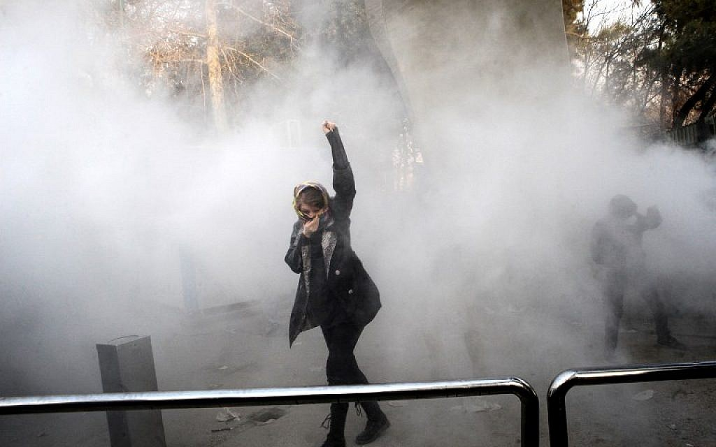 An Iranian woman raises her fist amid the smoke of tear gas at the University of Tehran during a protest driven by anger over economic problems, in the capital Tehran, December 30, 2017. (AFP/STR)