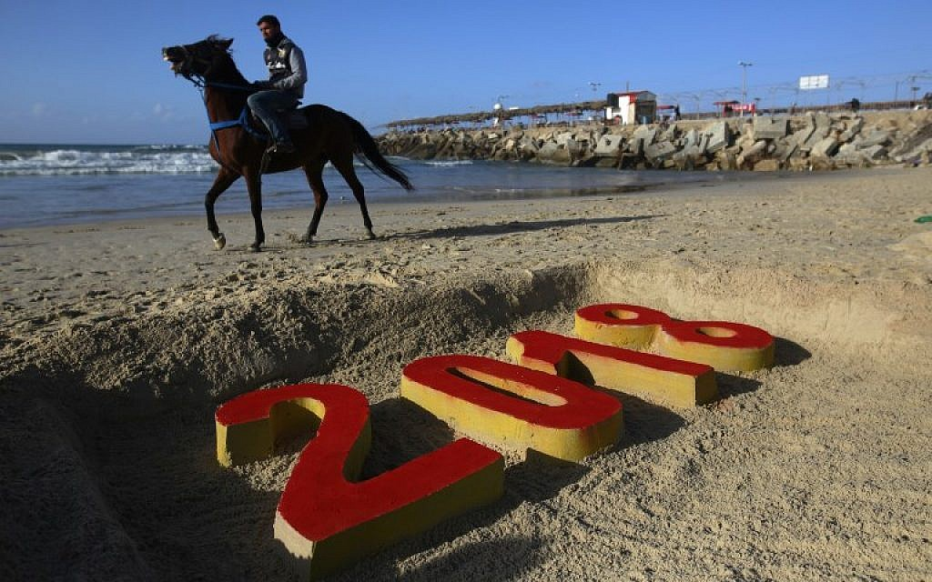 A Palestinian man walks past a 2018 sand writing at a beach in Gaza City on December 31, 2017 on the last day of the year. (AFP PHOTO / MOHAMMED ABED)