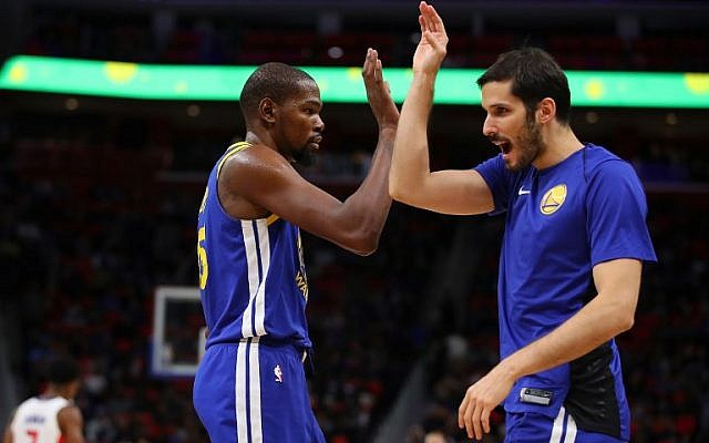 Kevin Durant #35 of the Golden State Warriors celebrates a second half basket with Omri Casspi #18 while playing the Detroit Pistons at Little Caesars Arena on December 8, 2017 in Detroit, Michigan. (Gregory Shamus/Getty Images/AFP)