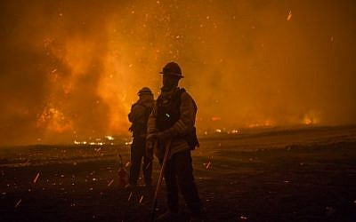 Embers fall on firefighters setting a backfire at night to make progress against the Thomas Fire before the winds return with the daylight near Lake Casitas on December 9, 2017 near Ojai, California. (David McNew/Getty Images/AFP)
