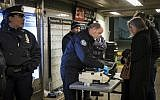 Members of the Transportation Security Administration and New York City Police Department check the bags of passengers as they enter the Times Square subway station during the evening rush hour, on December 11, 2017. (Drew Angerer/Getty Images/AFP)