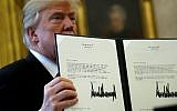 US President Donald Trump holds up a copy of legislation before signing the tax reform bill into law in the Oval Office December 22, 2017 in Washington, DC. (Chip Somodevilla/Getty Images/AFP)