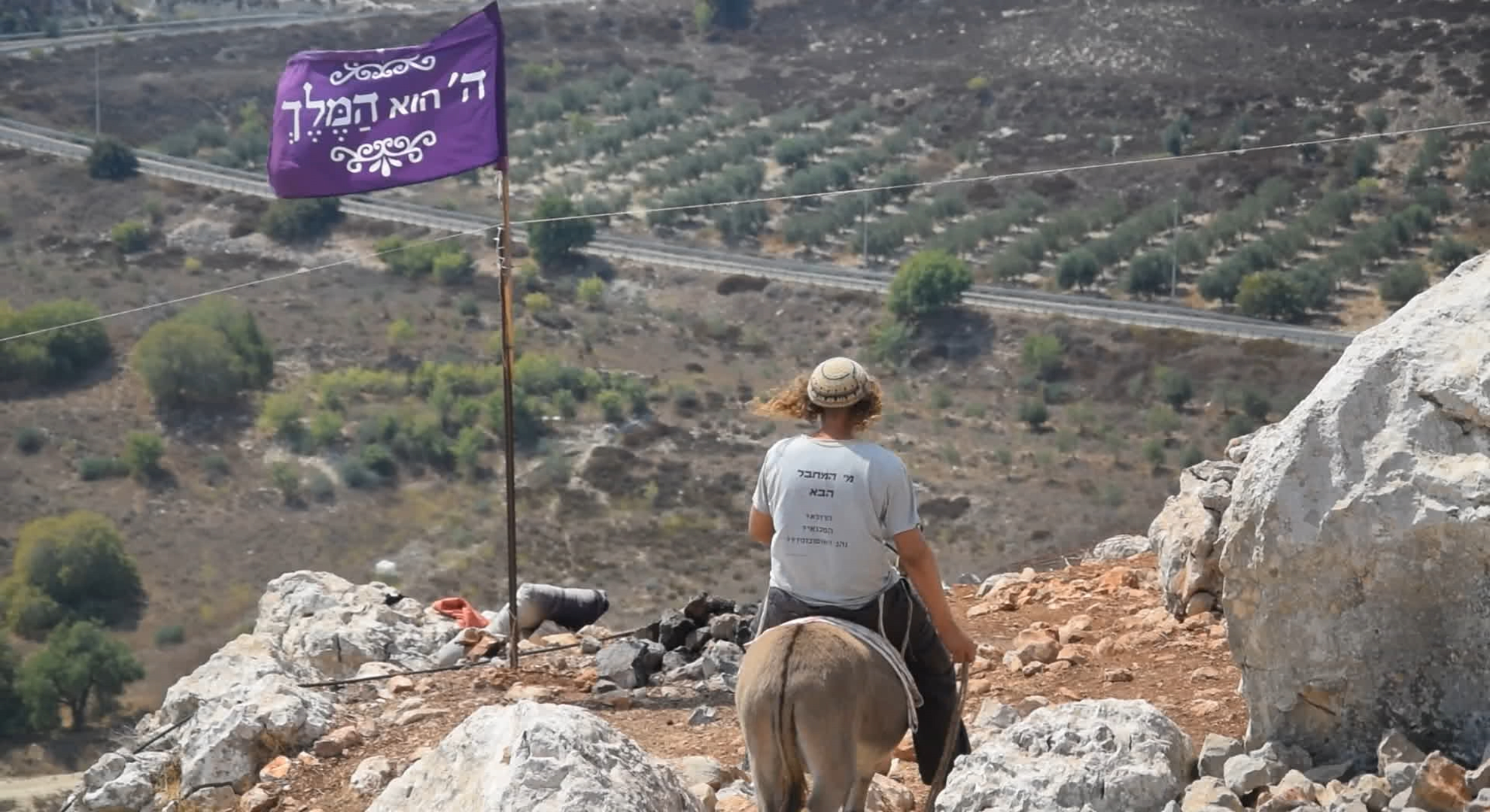 """Illustrative: A member of the """"hilltop youth"""" rides a donkey at an illegal outpost in the northern West Bank. (Credit: Zman Emet, Kan 11)"""