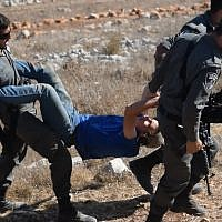 "Illustrative: Border Police carry away a member of the ""hilltop youth"" during an evacuation of an illegal outpost in the northern West Bank. (Credit: Zman Emet, Kan 11)"