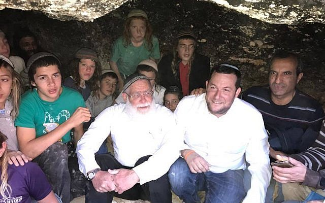 (From R-L) Yesha chairman Hananel Dorani, Samaria Regional Council chairman Yossi Dagan, and Samaria Rabbi Elyakim Levanon pose for a photo on December 8, 2017, with children in the same cave where they were attacked last week during clashes with Palestinians from Qusra. (Jacob Magid/Times of Israel)