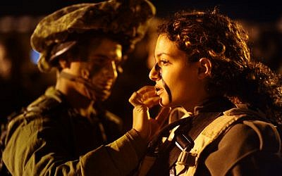 A male soldier from the co-ed Caracal Battalion applies camoflage paint to a female soldier's face before an exercise in 2011. (Ori Shifrin/Israel Defense Forces/Flickr)