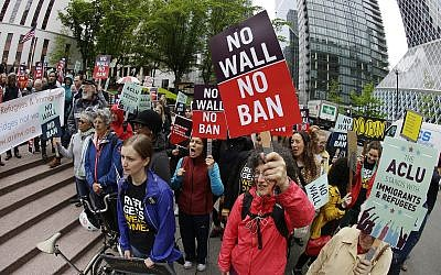 In this file photo from May 15, 2017, protesters wave signs and chant during a demonstration against US President Donald Trump's revised travel ban outside a federal courthouse in Seattle. (AP Photo/Ted S. Warren, File)
