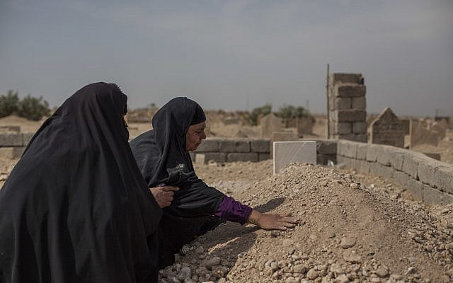 Fatima Ahmed Aswad cries as she touches the grave of her 15-year-old daughter Sana in Mosul on October 9, 2017. Sana's death, like those of  many civilians killed during the final battle to drive out Islamic State extremists, was not recorded until her body could be exhumed. An AP investigation found between 9,000 and 11,000 civilians died during the final battle to drive out Islamic State extremists. (AP Photo/Bram Janssen)