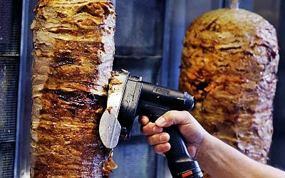 A man slices cuts of meat from a shawarma spit inside a restaurant cafe in Frankfurt, Germany, Thursday, November 30, 2017 (AP Photo/Michael Probst)