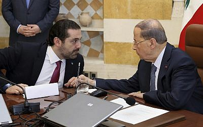 In this photo released by the Lebanese Government, Lebanese President Michel Aoun, right, speaks with Prime Minister Saad Hariri, at the Presidential Palace in Baabda, east of Beirut, Lebanon, on December 5, 2017. (Dalati Nohra/Lebanese Government via AP)