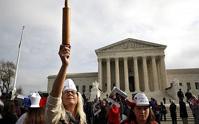 Mary Torres of Falls Church, Va., left, holds a rolling pin up in support of cake artist Jack Phillips, while outside of the Supreme Court with her daughter Maria Torres, right, Tuesday, Dec. 5, 2017, during arguments the 'Masterpiece Cakeshop v. Colorado Civil Rights Commission' case in Washington. (AP Photo/Jacquelyn Martin)