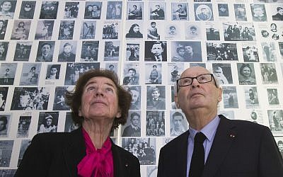In this December 5, 2017, photo, French Nazi hunters Beate Klarsfeld (l) and her husband Serge look at at photos of young Jews deported from France at the Shoah Memorial in Paris, France. (AP Photo/Michel Euler)