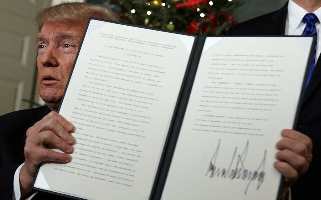 US President Donald Trump holds up a proclamation to officially recognize Jerusalem as the capital of Israel, in the Diplomatic Reception Room of the White House, on Dec. 6, 2017. (AP Photo/Evan Vucci)
