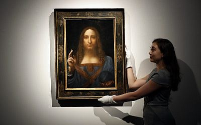 "In this October 24, 2017 photo, an employee poses with Leonardo da Vinci's ""Salvator Mundi"" on display at Christie's auction rooms in London. (AP Photo/Kirsty Wigglesworth)"
