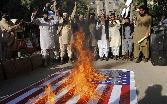 Pakistanis burn a representation of the US flag during a protest rally in Hyderabad, Pakistan, December 7, 2017. (AP Photo/Pervez Masih)