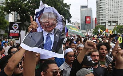 Muslims crumple a portrait of US President Donald Trump during a protest outside the US Embassy in Kuala Lumpur, Malaysia, December 8, 2017. (AP Photo/Sadiq Asyraf)