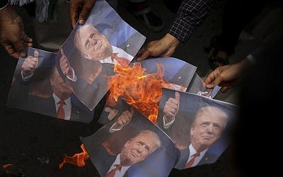 Muslim men burn portraits of US President Donald Trump and rally against his decision to recognize Jerusalem as Israel's capital in Banda Aceh, Indonesia, Friday, Dec. 8, 2017. (AP Photo/Heri Juanda)