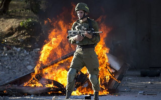 Israeli soldier stands during clashes with Palestinians following a protest against US President Donald Trump's decision to recognize Jerusalem as the capital of Israel in the West Bank City of Nablus, Friday, Dec. 8, 2017. (AP Photo/Majdi Mohammed)