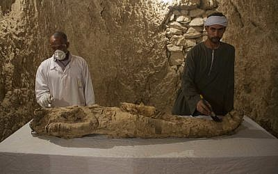 "Egyptian excavation workers restore a mummy in a newly discovered tomb on Luxor's West Bank known as ""KAMPP 150,"" December 9, 2017. (AP Photo/Hamada Elrasam)"