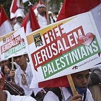 Muslim men hold posters during a rally against US President Donald Trump's decision to recognize Jerusalem as Israel's capital outside the US Embassy in Jakarta, Indonesia, December 10, 2017. (AP Photo/Dita Alangkara)