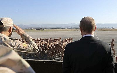 Russian President Vladimir Putin, right, watches the troops marching as he and Syrian President Bashar Assad visit the Hmeimim air base in Syria, December 11, 2017. (Mikhail Klimentyev, Sputnik, Kremlin Pool Photo via AP)