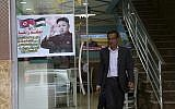 A Palestinian customer walks out of a shawarma restaurant with a poster of North Korean leader Jim Jong in Jebaliya refugee camp, Gaza Strip, December 14, 2017. (AP Photo/Adel Hana)