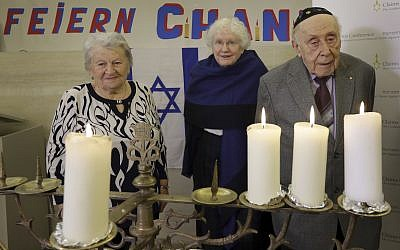 From left, Holocaust survivors Assia Gorban, Marlene Herzberg and Rudolf Rosenberg attend a reception and Hanukkah candle lighting at the Jewish Community Center, in Berlin, Germany, Thursday, Dec. 14, 2017.  (AP Photo/Michael Sohn)