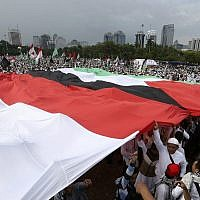 Protesters hold Indonesian and Palestinian flags during a rally against US President Donald Trump's recognition of Jerusalem as Israel's capital at Monas, the national monument, in Jakarta, Indonesia, on December 17, 2017. (AP Photo/Achmad Ibrahim)