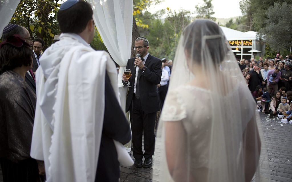 In this Thursday, December 14, 2017 photo, Rabbi Chuck Davidson holds a wedding service in Ein Hemed. A growing number of Israeli couples are defying the country's Chief Rabbinate and marrying in unsanctioned weddings. (AP Photo/Ariel Schalit)