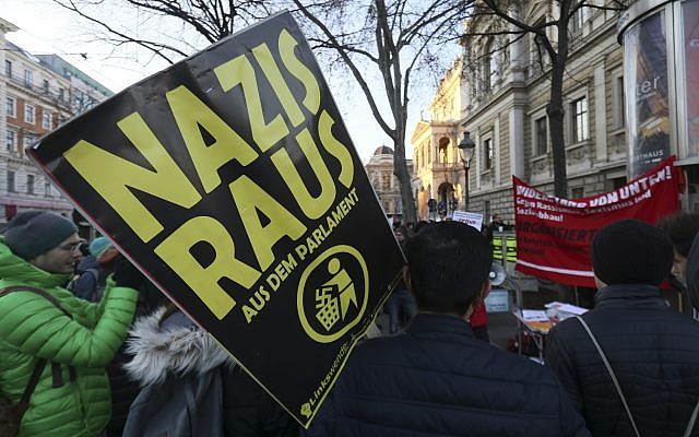 A demonstrator holds a poster 'Nazis out of the parliament' during a demonstration prior to the swearing-in ceremony of the new Austrian government led by a conservative and a nationalist party in Vienna, Austria, December 18, 2017. (Ronald Zak/AP)